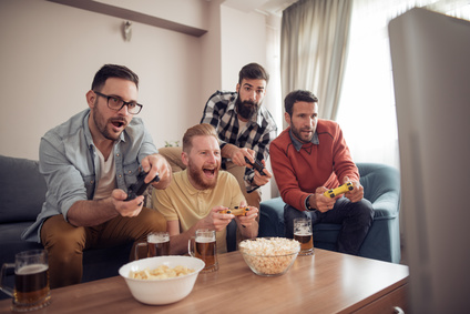 Happy young male friends playing video games at home,having fun.
